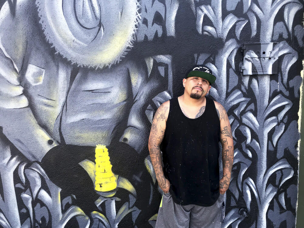 Graffiti artist Lesho poses for a photo in front of one of his murals at the Graff Lab in the Pico Union neighborhood of Los Angeles.
