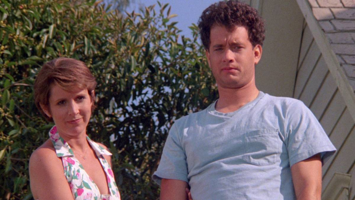 Carrie Fisher and Tom Hanks next to a suburban house.