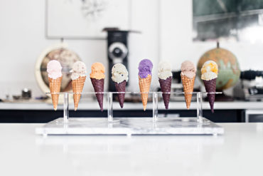 A row of eight colorful ice cream cones on a countertop cone holder.