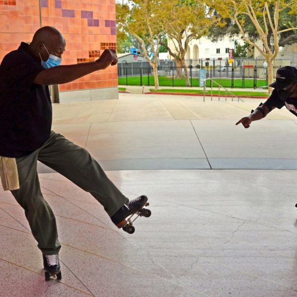 Two adult men balance mid-motion on their roller skates at an outdoor park.