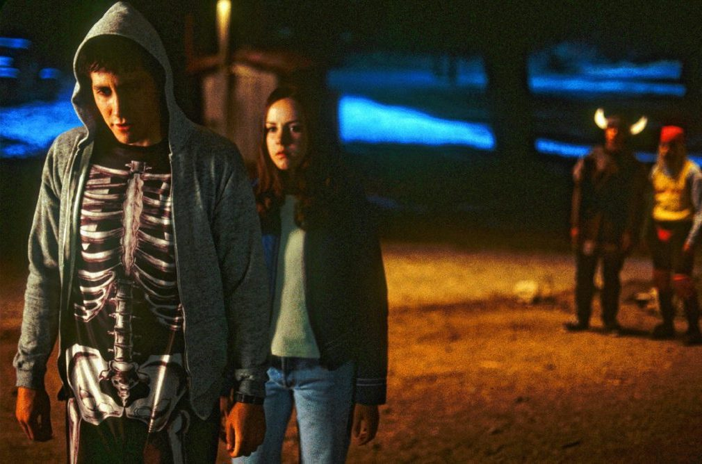 A young man and woman stand on a street at night. Behind them are two onlookers.