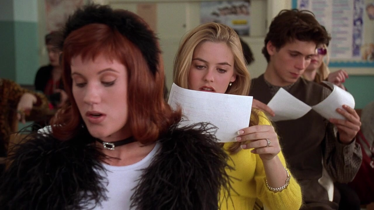 """From the movie """"Clueless,"""" three high schoolers sit in a row of desks and hold up papers to their faces."""