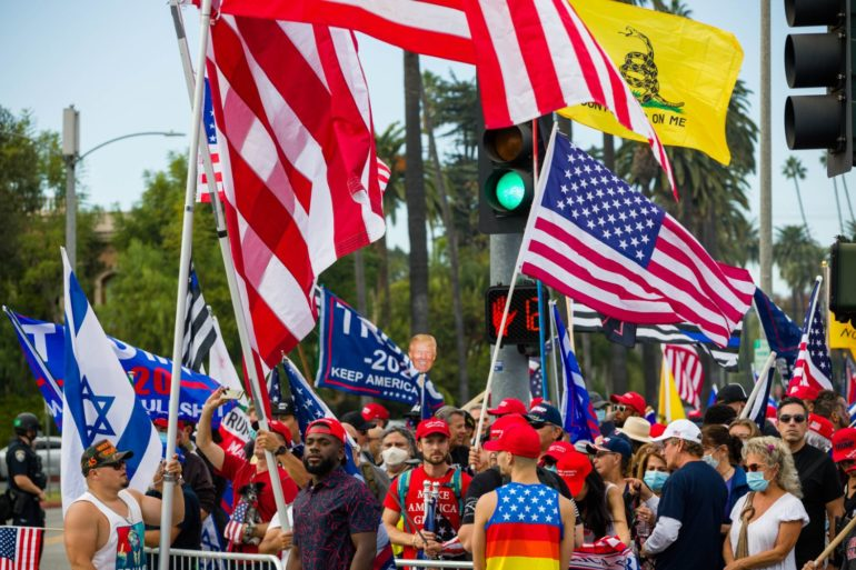 """A crowd of people gathered on the sidewalk, waving United States flags, Trump 2020 flags, a """"Don't tread on me"""" flag, and an Israel flag. Many also wear red """"Make America Great Again"""" hats."""